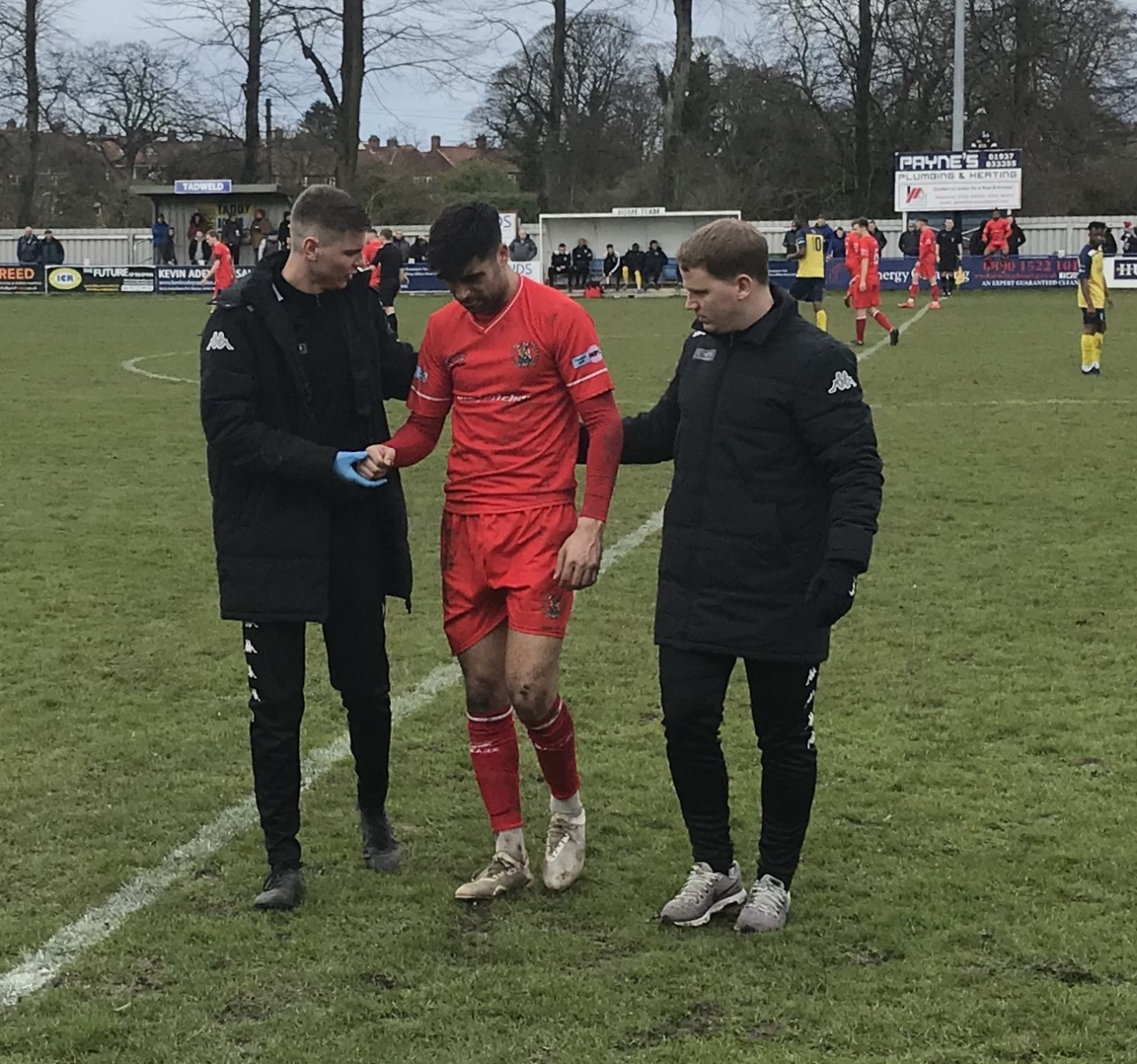 Tadcaster-AlbionRonan-Irving-and-Steven-Rudd-escort-the-injured-Nathan-Waterston-off-the-pitch